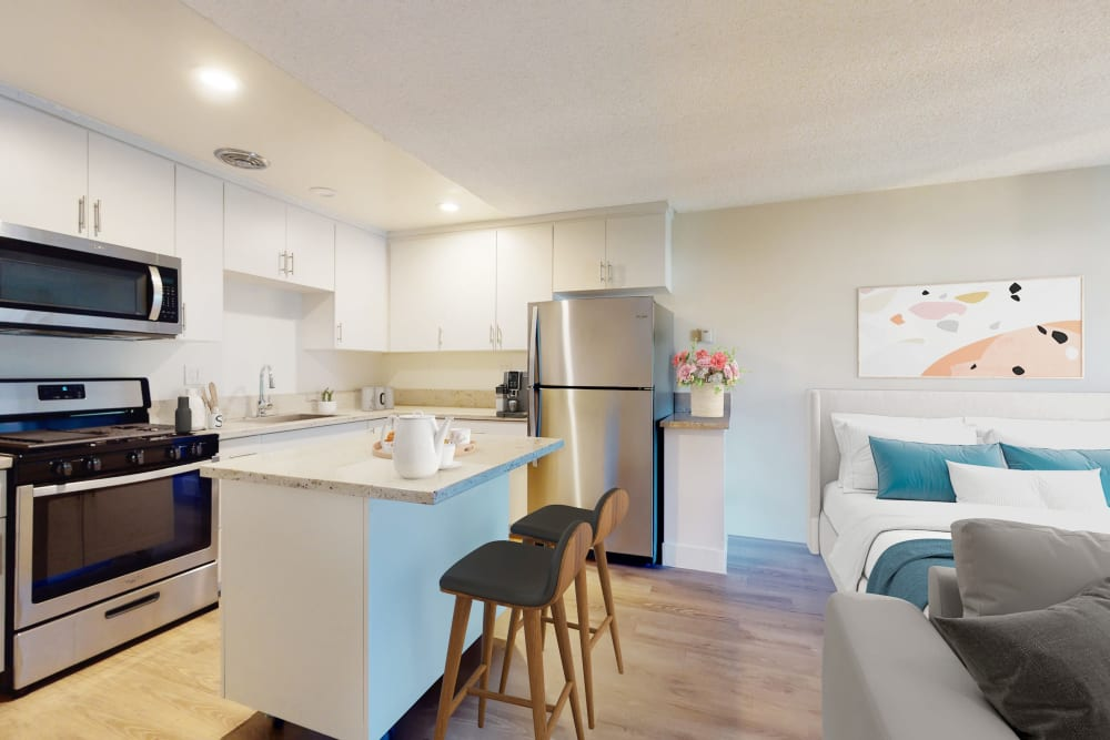 Stainless-steel appliances and bright white cabinetry in a studio apartment's kitchen at Mediterranean Village in West Hollywood, California