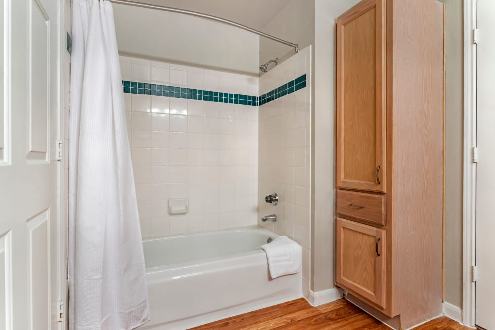 Bathroom with tub and shower combination and linen cabinet at Regency at First Colony in Sugar Land, Texas