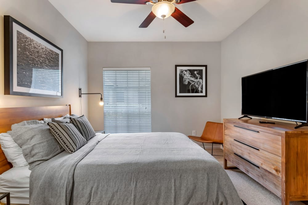 Model bedroom with ceiling fan and a large flat screen television on a dresser at Regency at First Colony in Sugar Land, Texas