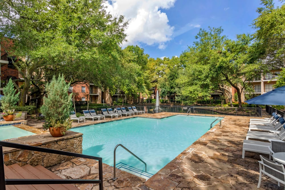 Sparkling swimming pool next to a lake surrounded by mature trees and lush landscaping at Foundations at River Crest & Lions Head in Sugar Land, Texas
