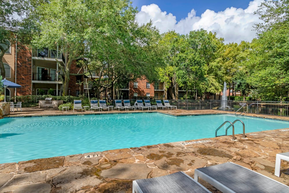 Stunning swimming pool next to a lake and water feature at Foundations at River Crest & Lions Head in Sugar Land, Texas
