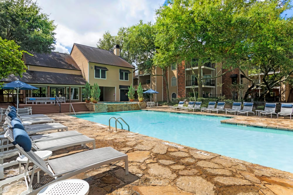 Swimming pool with expansive sundeck and plenty of lounge chairs at Foundations at River Crest & Lions Head in Sugar Land, Texas