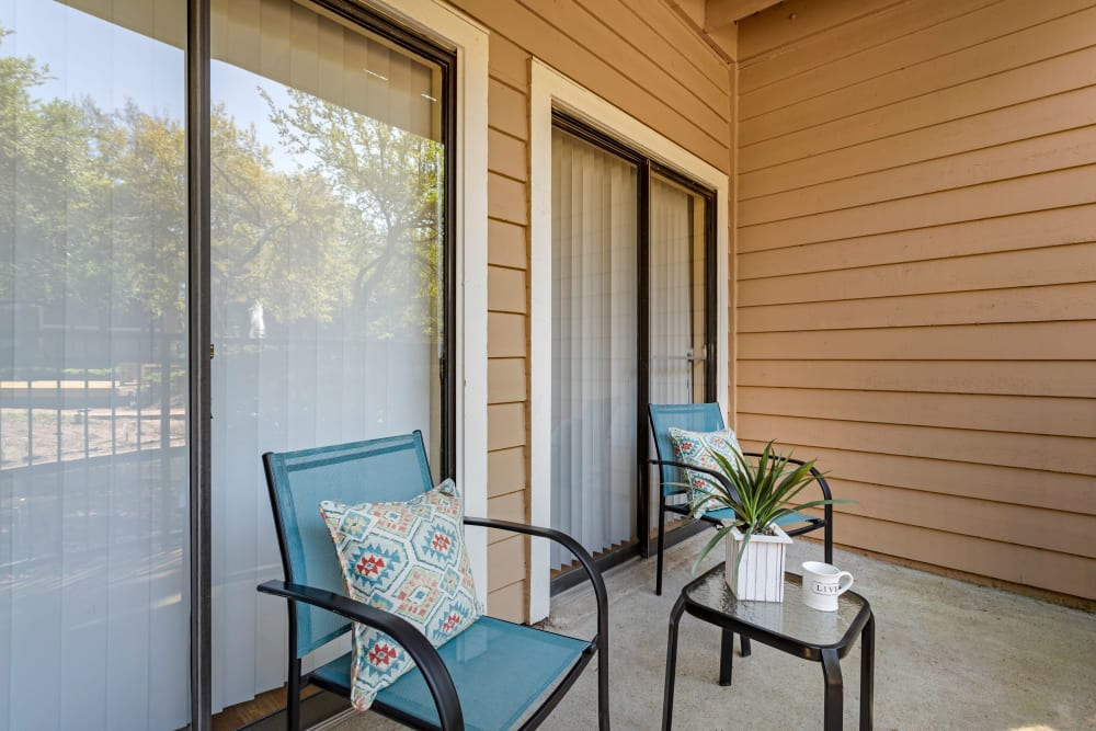 Spacious private patio with table and chairs outside an apartment home at Foundations at River Crest & Lions Head in Sugar Land, Texas