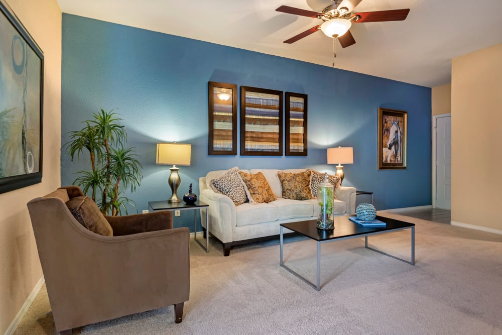 Well decorated living room with ceiling fan and plush carpeting at Foundations at River Crest & Lions Head in Sugar Land, Texas