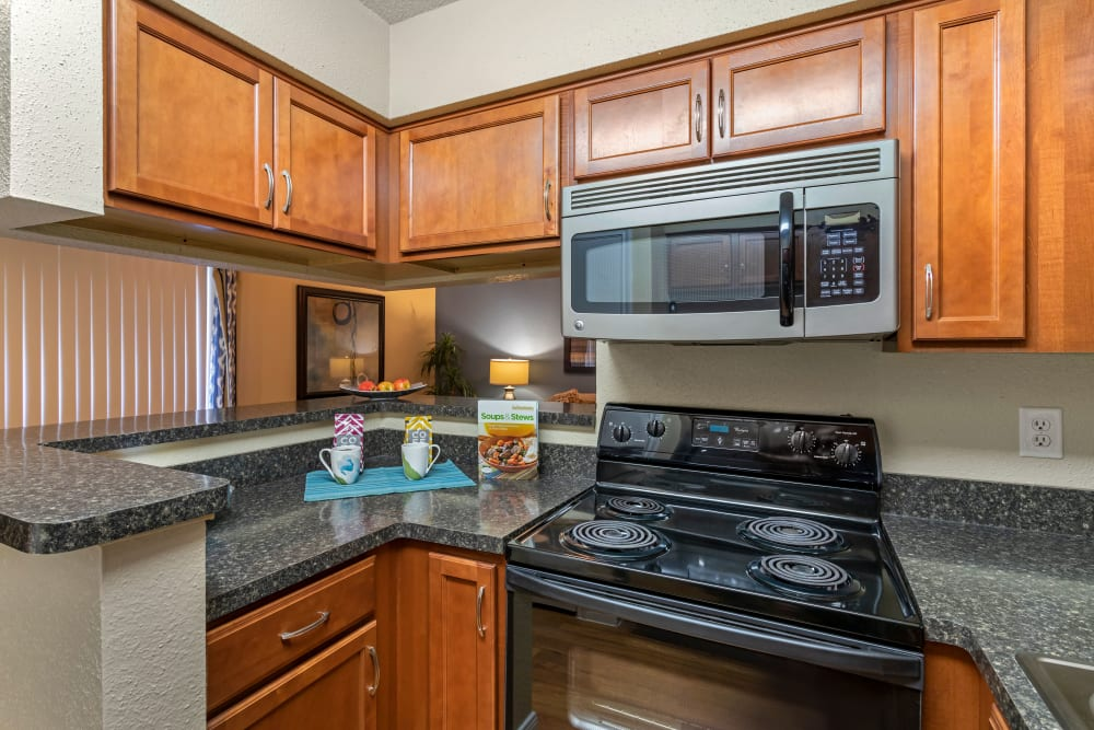 Fully equipped kitchen with built-in microwave and custom cabinetry at Foundations at River Crest & Lions Head in Sugar Land, Texas