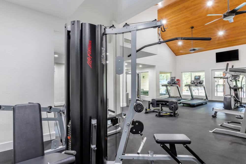 Fully equipped fitness center with ceiling fans and a large TV at Foundations at River Crest & Lions Head in Sugar Land, Texas