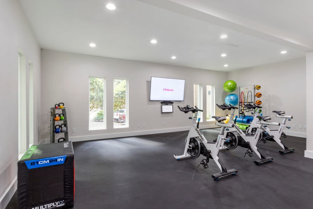 Spin bikes in front of a wall mounted TV and a variety of fitness equipment at Foundations at River Crest & Lions Head in Sugar Land, Texas