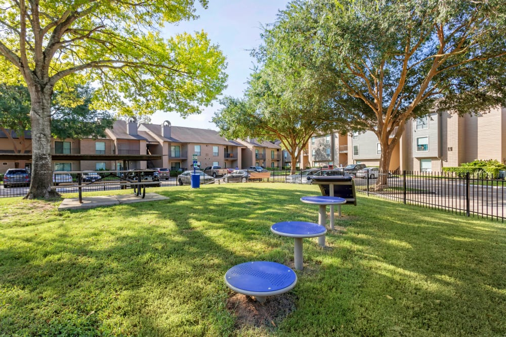 Bark park with a picnic table and agility equipment at Foundations at River Crest & Lions Head in Sugar Land, Texas