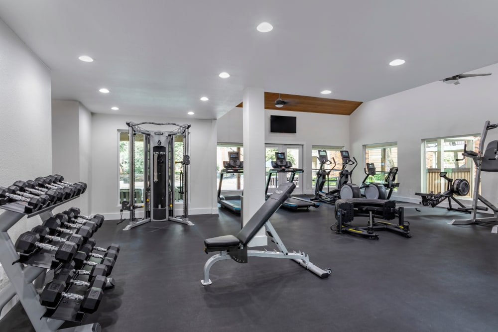 Weights and a variety of state-of-the-art equipment and machines in the fitness center at Foundations at River Crest & Lions Head in Sugar Land, Texas
