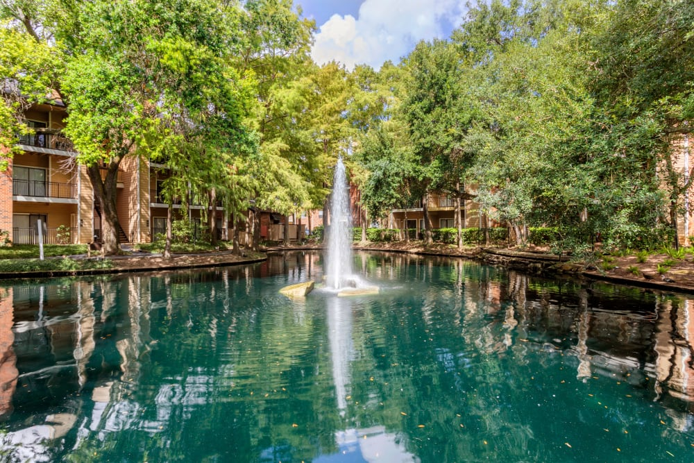 Lagoon-style lake with water feature surrounded by mature trees in the courtyard of Foundations at River Crest & Lions Head in Sugar Land, Texas