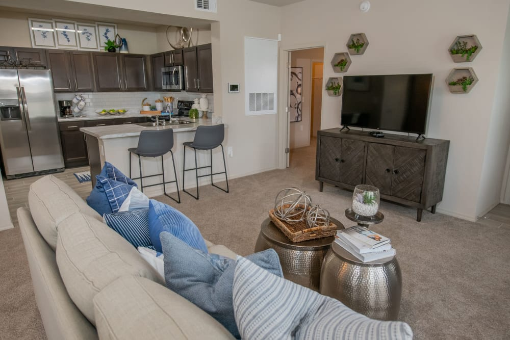 Well-furnished living space with plush carpeting in a model home at Redbud Ranch Apartments in Broken Arrow, Oklahoma