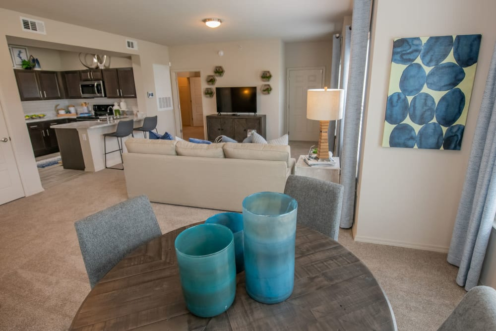 View of the spacious open-concept living area from the dining nook in a model apartment at Redbud Ranch Apartments in Broken Arrow, Oklahoma
