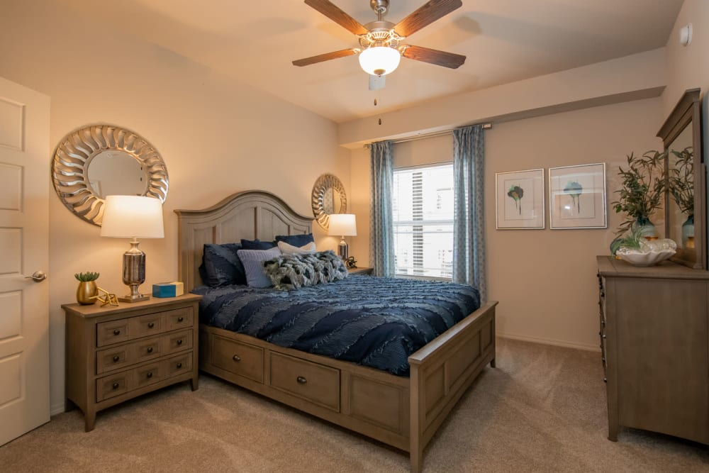 Plush carpeting, draped window, and a ceiling fan in the primary suite of a model apartment at Redbud Ranch Apartments in Broken Arrow, Oklahoma
