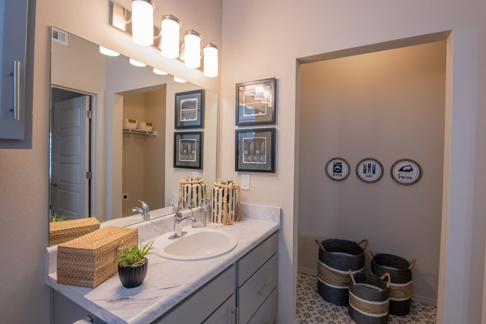 Large vanity mirror and a granite countertop in a model home's bathroom at Redbud Ranch Apartments in Broken Arrow, Oklahoma