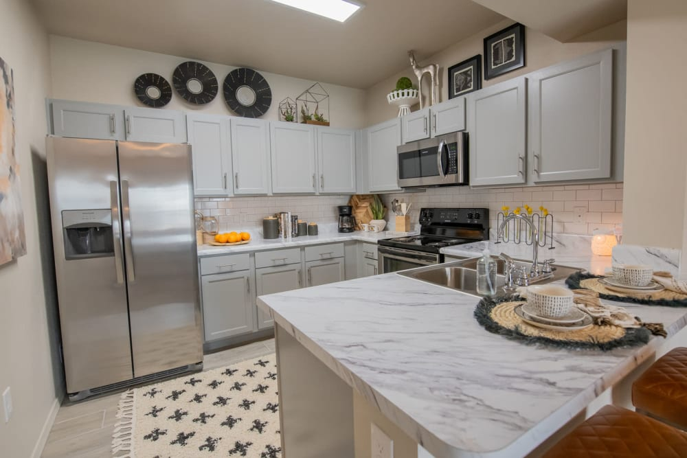 Ceramic tile flooring and custom wood cabinetry in a model home's kitchen at Redbud Ranch Apartments in Broken Arrow, Oklahoma