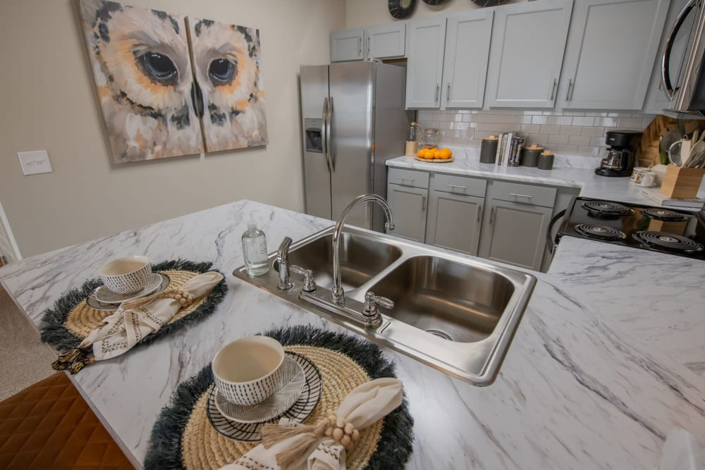 Model apartment's kitchen with granite countertops and stainless-steel appliances at Redbud Ranch Apartments in Broken Arrow, Oklahoma