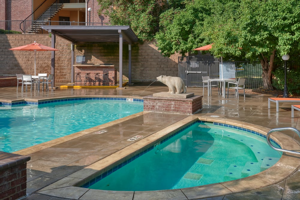 Beautiful resort-style swimming pool with lounge chairs at The Crossings at Bear Creek Apartments in Lakewood, Colorado