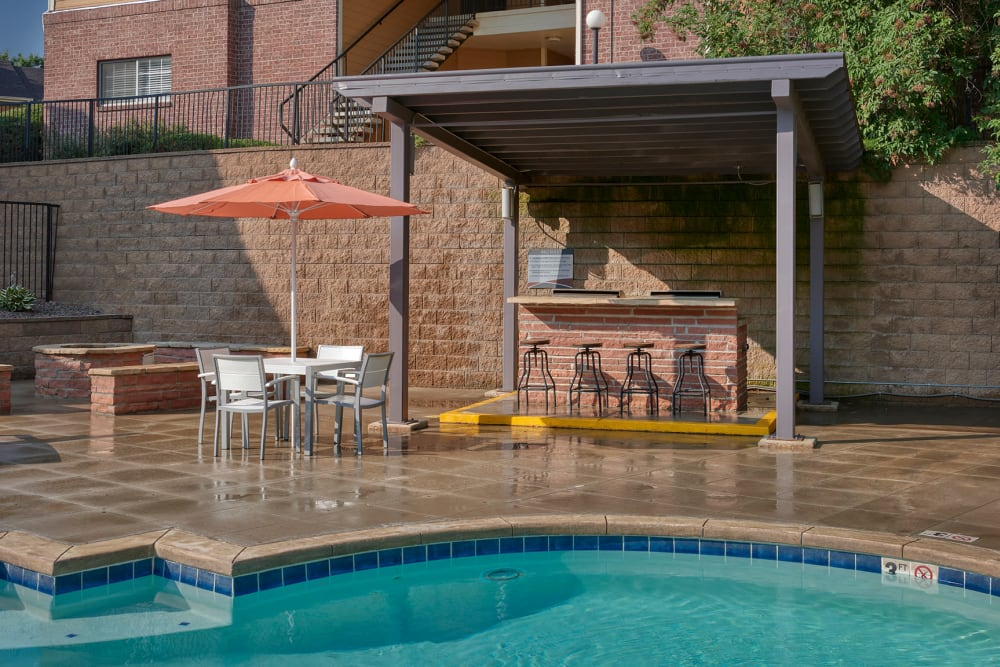 Swimming pool with a sundeck, lounge chairs, BBQ, and Fire Pit at The Crossings at Bear Creek Apartments in Lakewood, Colorado
