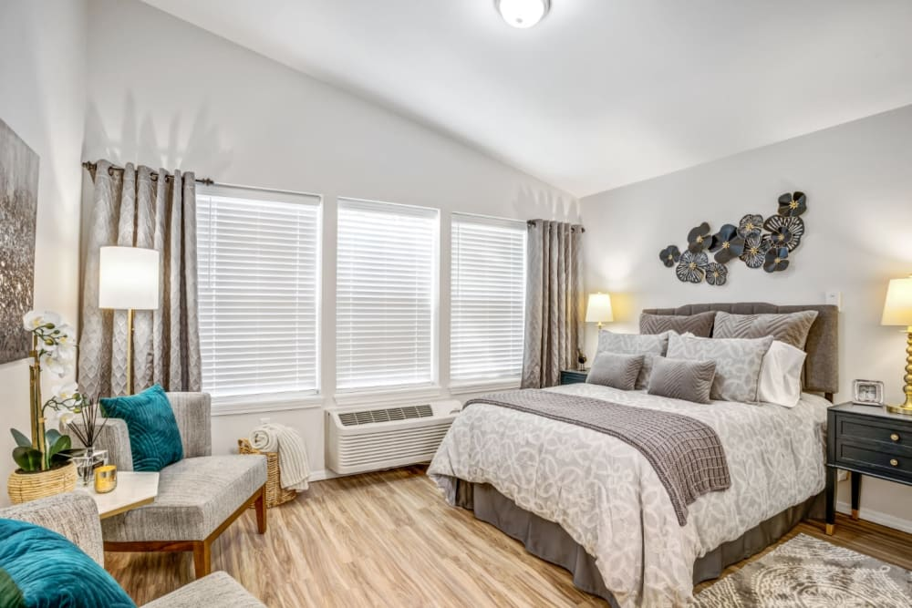 Bright bedroom with large windows at Woodside Senior Living in Springfield, Oregon