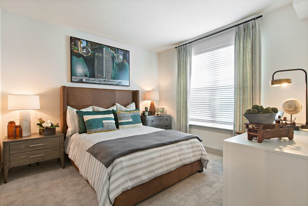 Well lit bedroom with carpet and huge windows at 8 Metro Station in Charlotte, North Carolina