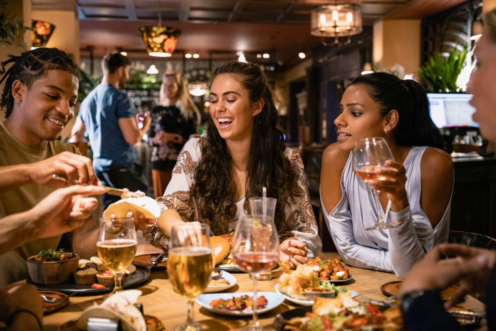 Resident friends gathered for dinner and drinks at their favorite restaurant near Fields on 15th Apartment Homes in Longmont, Colorado