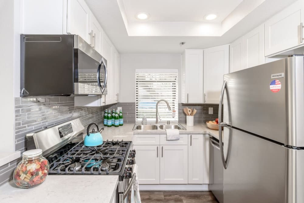 Stainless steel appliances and white sleek looking cabinets in the kitchen at Sendero Huntington Beach in Huntington Beach, California