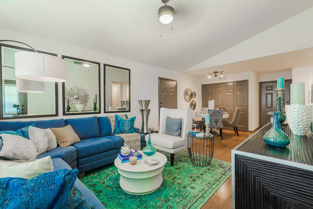 Colorful living room with a large blue couch and sea-green carpet at Sunstone Village in Denton, Texas