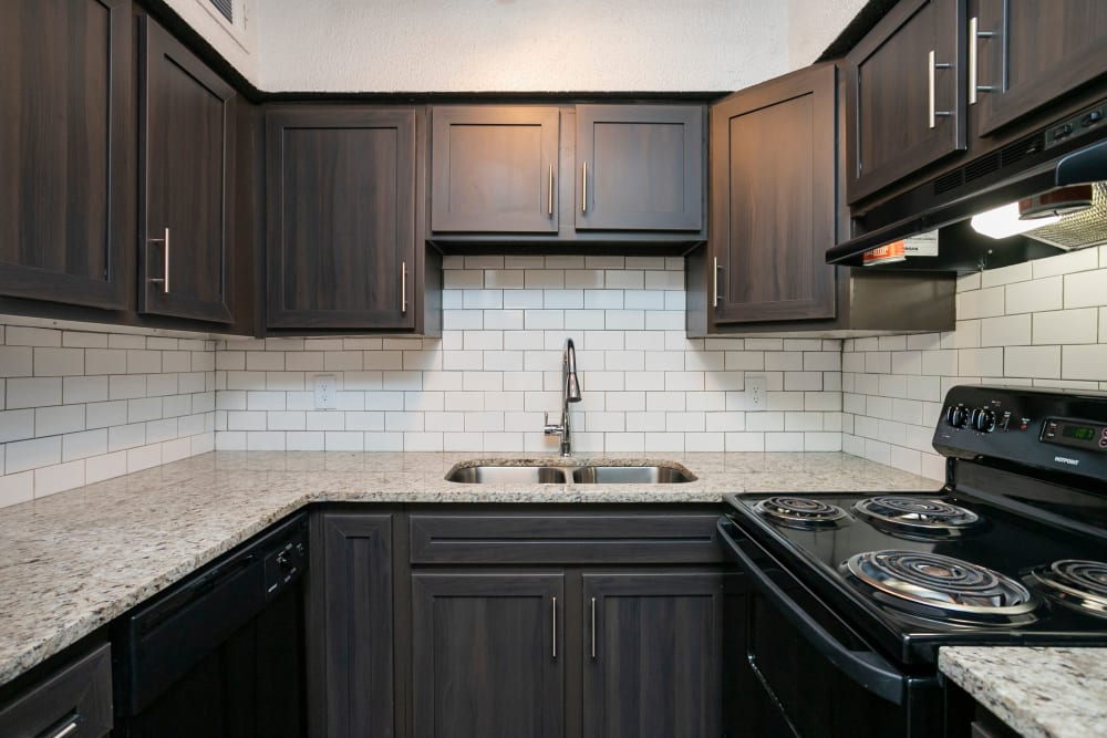 Upgraded kitchen with granite countertops and black appliances with a classic, subway tile backsplash at Magnolia Place Apartments in Franklin, Tennessee