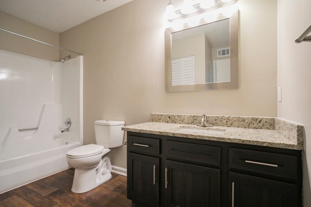 Bathroom with framed mirror and granite topped vanity at Magnolia Place Apartments in Franklin, Tennessee