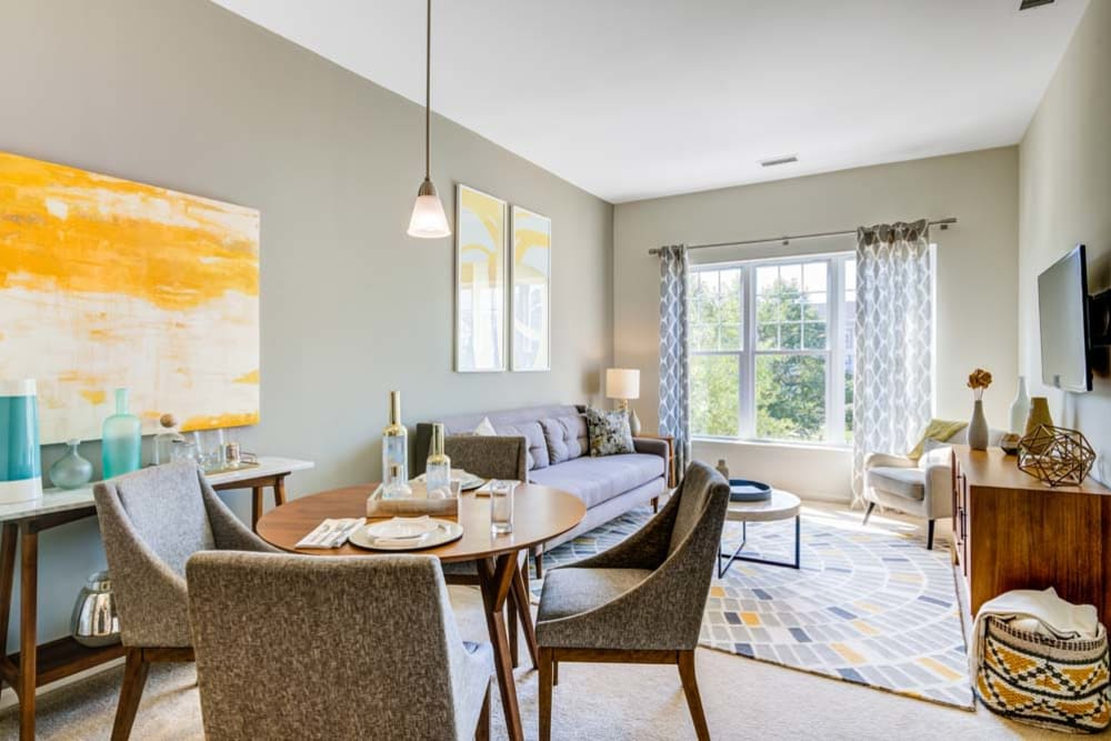 Dining room space and well decorated living room space featuring large window at The Grove Somerset in Somerset, New Jersey
