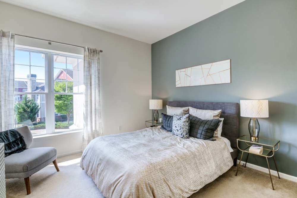 Spacious bedroom with green accent wall and large window for natural light at The Grove Somerset in Somerset, New Jersey