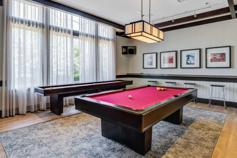 Interior of clubhouse featuring a billiards table and shuffleboard game at The Grove Somerset in Somerset, New Jersey