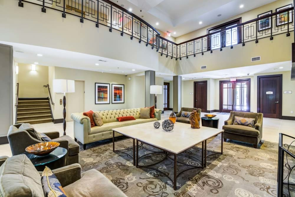 Interior of community clubhouse featuring balcony overlooks and spacious community common areas at The Grove Somerset in Somerset, New Jersey