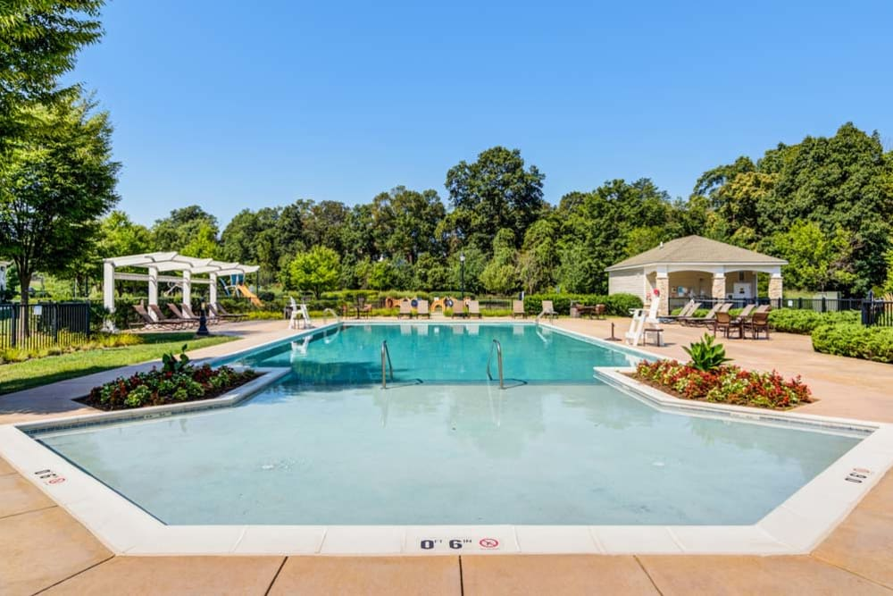 Outdoor community pool with lounge chairs and other amenities at The Grove Somerset in Somerset, New Jersey