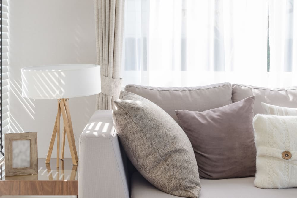 Couch and end table with morning light filtering through the drapes of a model home at K Street Flats Apartment Homes in Berkeley, California