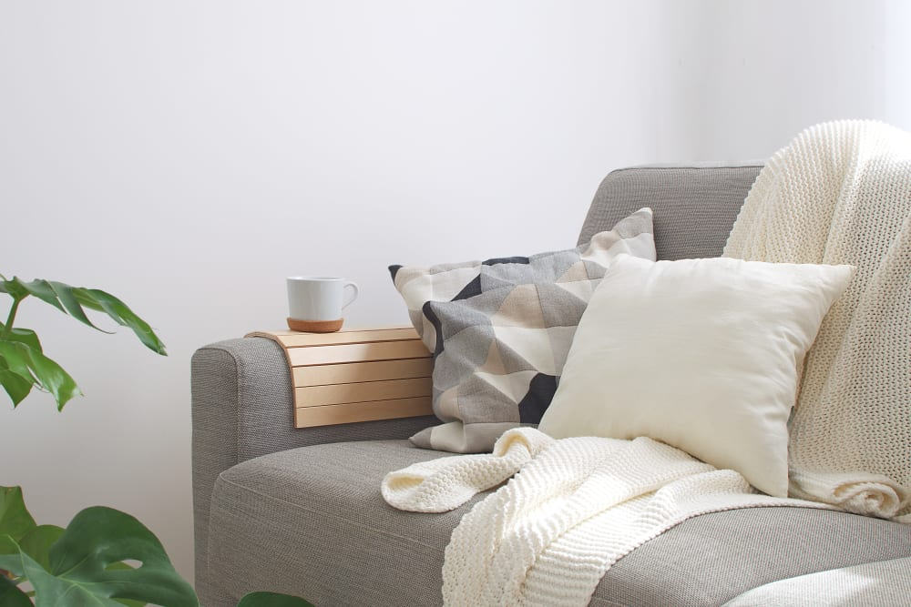 Couch with an arm caddy and a cup of tea on it in a model home at K Street Flats Apartment Homes in Berkeley, California