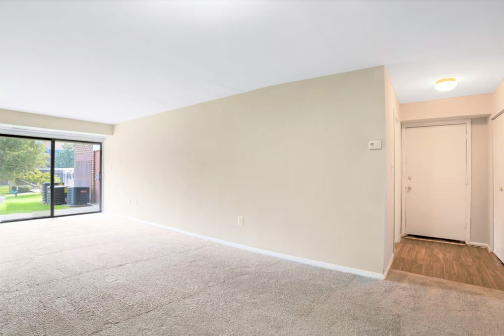 Apartment's spacious living area with a sliding door to the private patio outside at Eagle Rock Apartments at Towson in Towson, Maryland