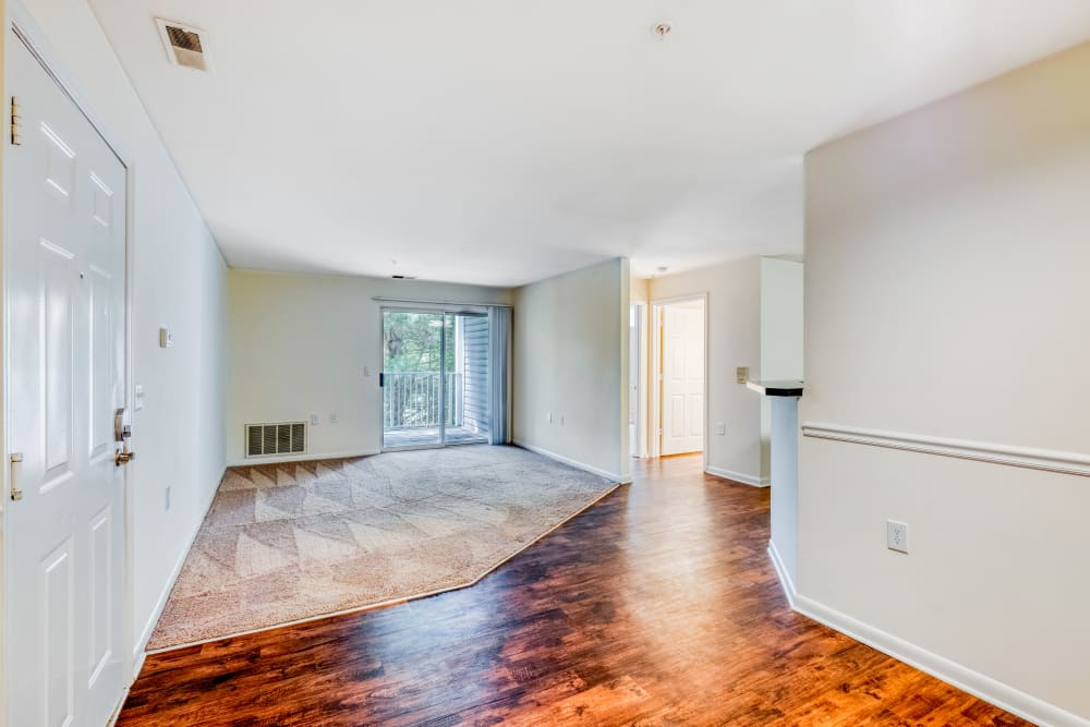 Interior vacant apartment home with large living room with fire place and view of patio at Park at Winterset Apartments in Owings Mills, Maryland