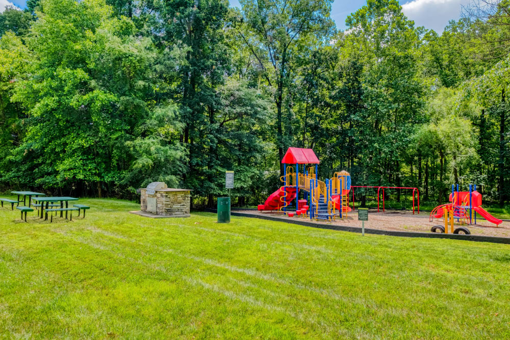 Exterior lush landscaping with a playground and bbq picnic area at Park at Winterset Apartments in Owings Mills, Maryland