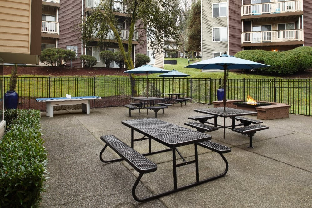 Barbecue area and outdoor ping pong table and fire pit at Park South Apartments in Seattle, Washington