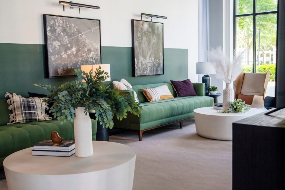 Very modern looking lounge area with nice green couch at The Flats at West Broad Village in Glen Allen, Virginia