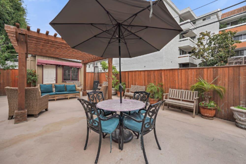 Table and chairs shaded by an umbrella at Meridian at Ocean Villa & Bella Mar in Santa Monica, California