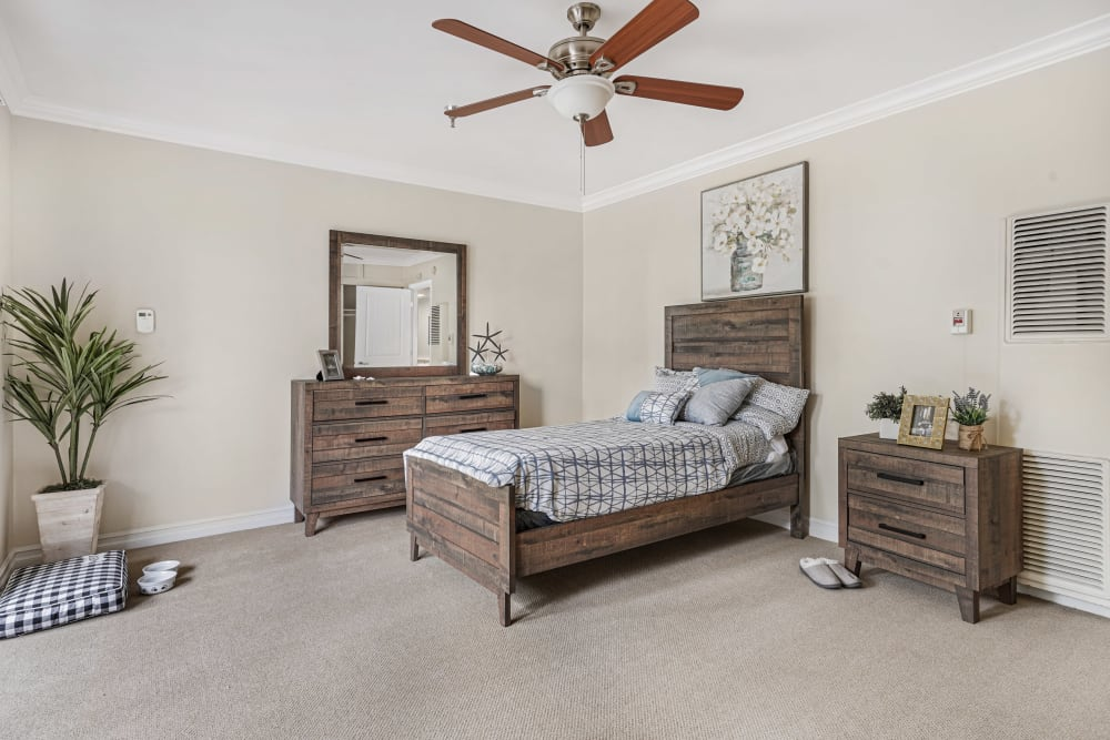 Large bedroom with wood style furniture and a ceiling fan at Meridian at Ocean Villa & Bella Mar in Santa Monica, California