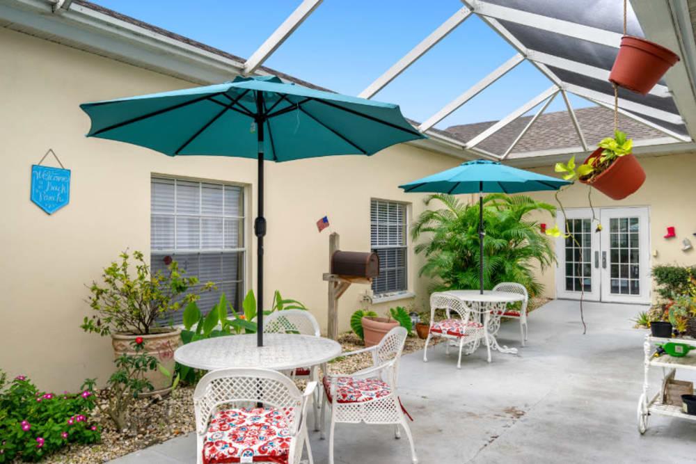 Tables and umbrellas in the courtyard at Truewood by Merrill, Bradenton in Bradenton, Florida