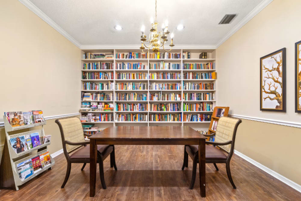 Table and a bookshelf in a small room at Truewood by Merrill, Bradenton in Bradenton, Florida