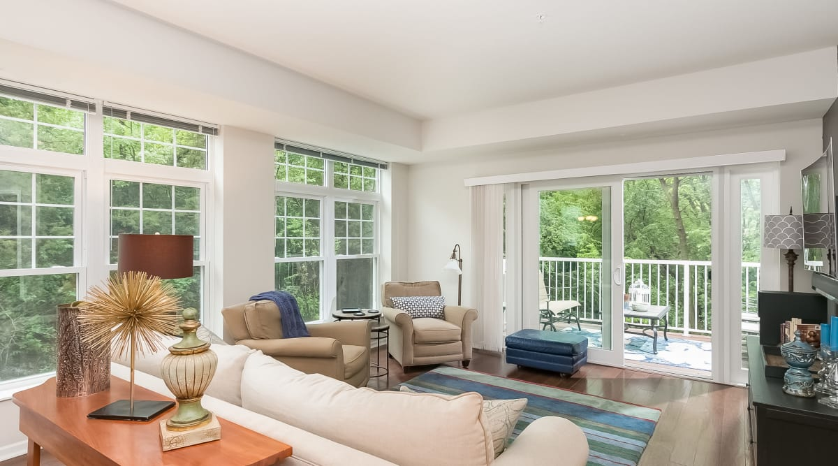 Spacious living room with scenic views and balcony access at Applewood Pointe of Lake Elmo in Lake Elmo, Minnesota