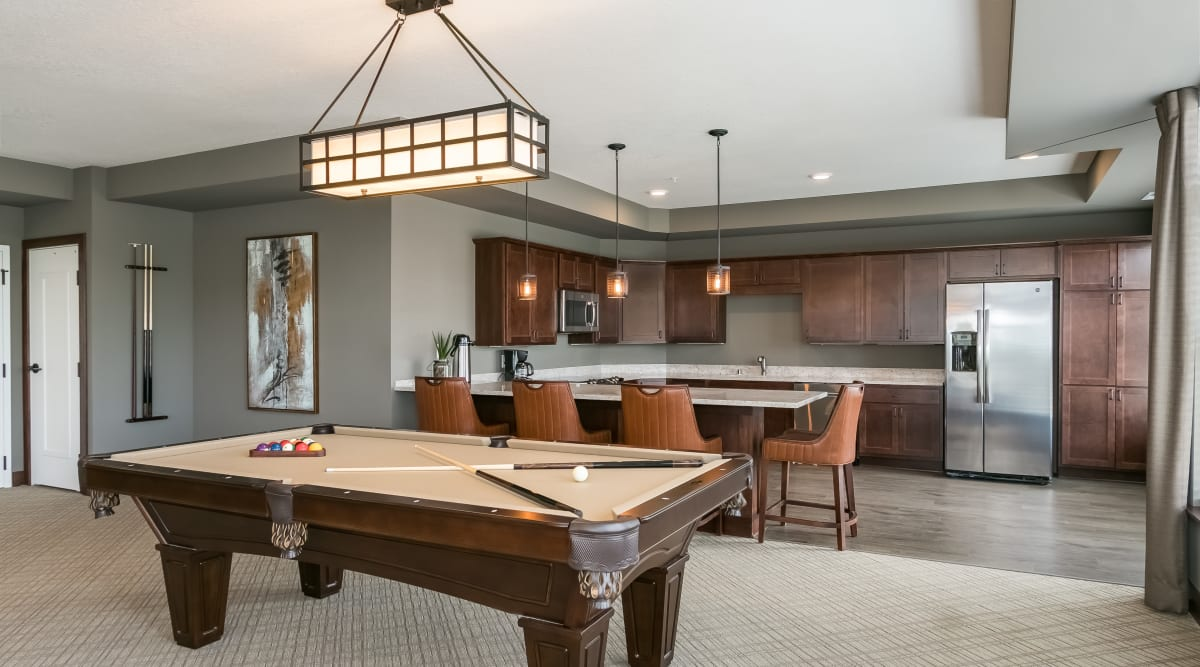 Billiards room and kitchen area at Applewood Pointe of Prior Lake in Prior Lake, Minnesota