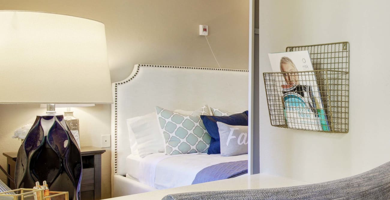 Well-lit model bedroom at Fairview Commons with decorative pillows.