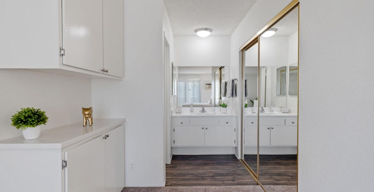 Large master bathroom with walk-in closet with mirror doors at The Esplanade in Lake Balboa, California
