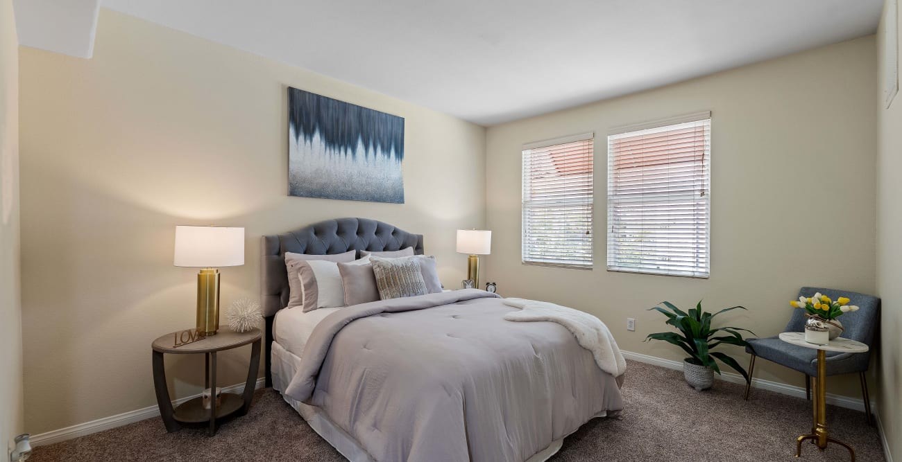 Carpeted bedroom with large window at The Villagio in Northridge, CA